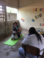 Helping with exercises for a child with cerebral palsy. There is no other help for her in the village.